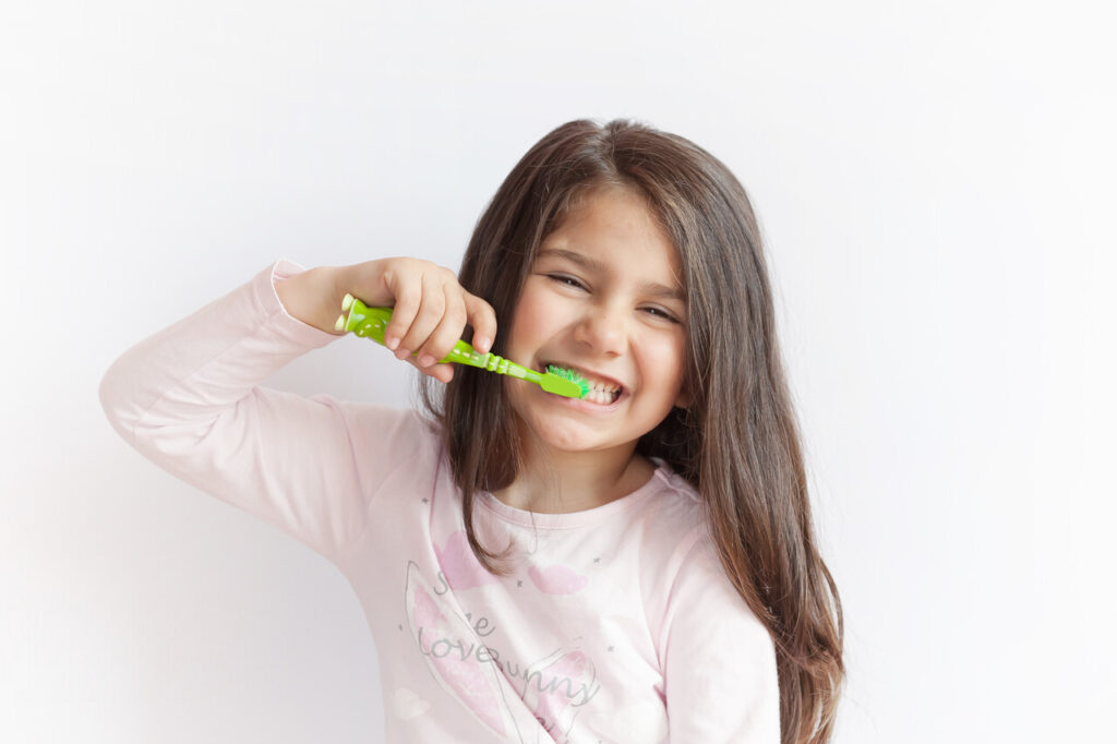 child girl brushing her teeth on white background. Space for text. Healthy teeth.
